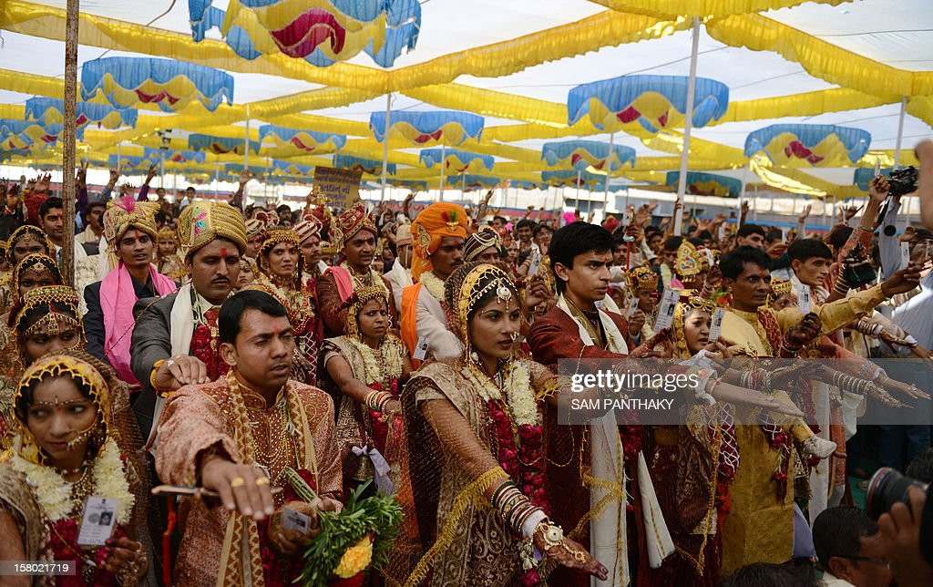 Indian brides and grooms hold their voter identity cards as they pledge to cast their vote in the forthcoming Gujarat Assembly elections after the marriage ceremony in Ahmedabad on December 9, 2012. Some 51 couples were married and pledged to vote along with their relatives in an event organised by Balkeshwar Mahadev Trust. Gujarat state goes to the polls in two phases, December 13 and 17, 2012. AFP PHOTO /Sam PANTHAKY