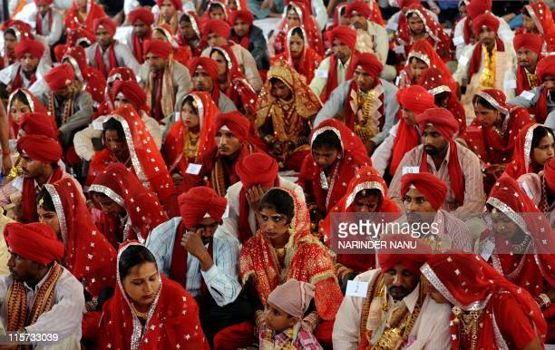Indian brides and grooms sit during a mass marriage ceremony for some 187 lowincome couples from the IndiaPakistan border area at Gurdwara Baba...