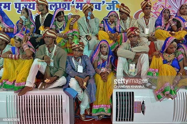 Indian brides and grooms wait for the start of a mass wedding in New Delhi on June 15 2014 Some 92 lowincome and disabled couples tied the knot in a...