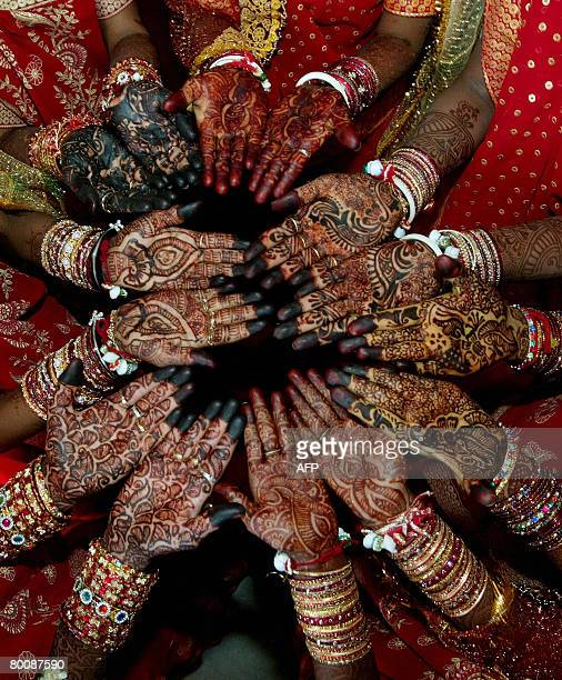 Indian brides display their hands decorated with henna in traditional bridal patterns prior to the start of a multi religious mass marriage in Bavla...