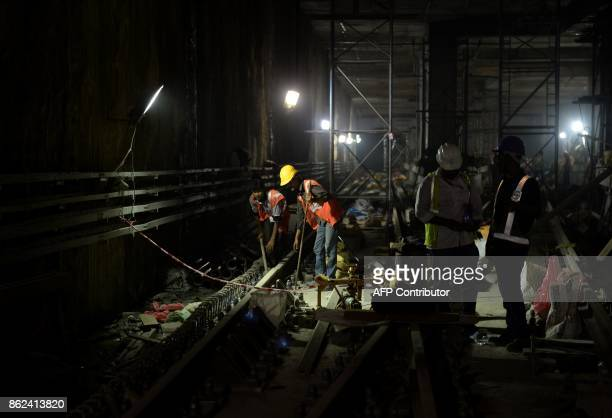Indian builders work in an underground tunnel under construction of the Chennai Metro Rail on October 17 2017 / AFP PHOTO / ARUN SANKAR