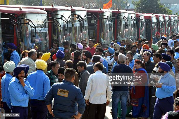 Indian bus drivers and political leaders gather during the inauguration of the City Bus Service in Amritsar on January 28 2014 The bus service will...