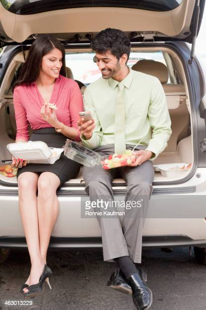Indian business people having lunch in trunk of car