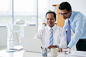 Indian business people working on laptop together