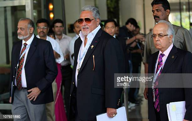 Indian businessman and owner of 'Royal Challengers Bangalore' Indian Premier League cricket team Vijay Mallya walks with officials as they arrive to...