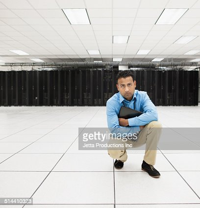 Indian businessman crouching in server room