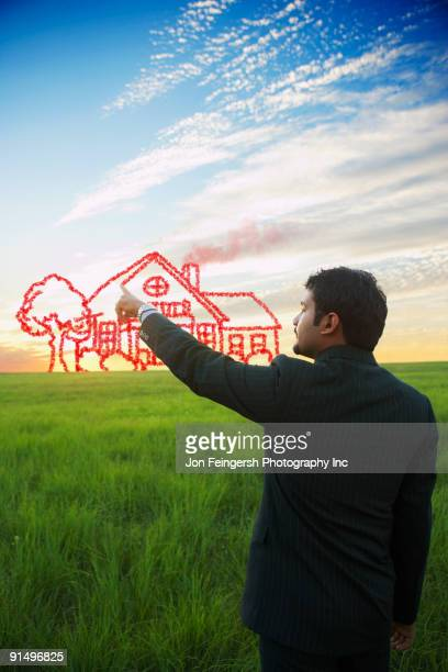 Indian businessman drawing house on sky
