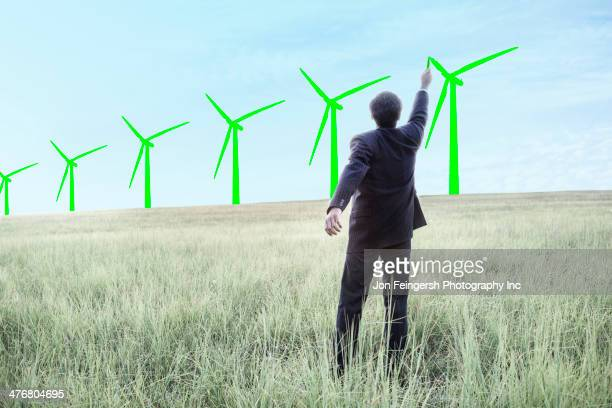 Indian businessman drawing wind turbines on sky