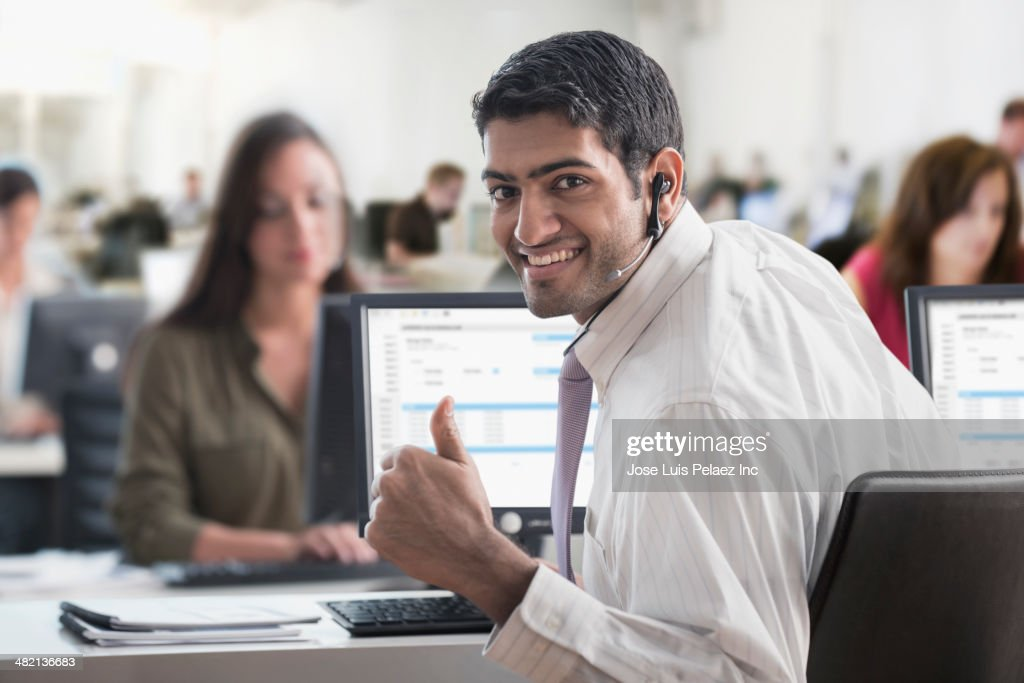 Indian businessman giving thumbs up in office