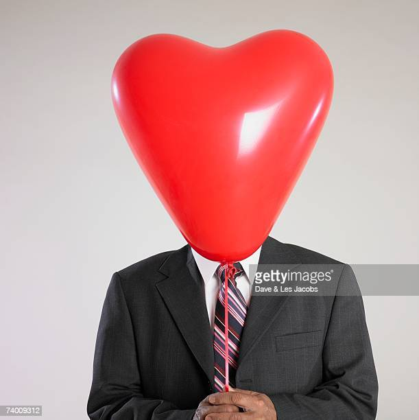 Indian businessman holding balloon in front of face