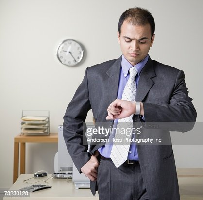 Indian businessman looking at watch next to desk