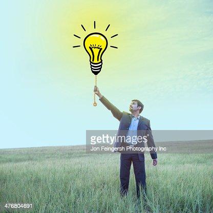 Indian businessman pulling chain on light bulb illustration