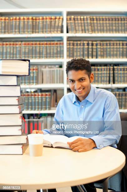 Indian businessman reading at desk in law library