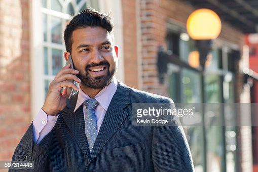 Indian businessman talking on cell phone in city