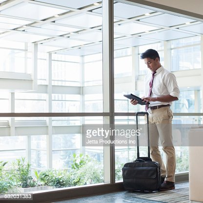 Indian businessman using digital tablet in office lobby
