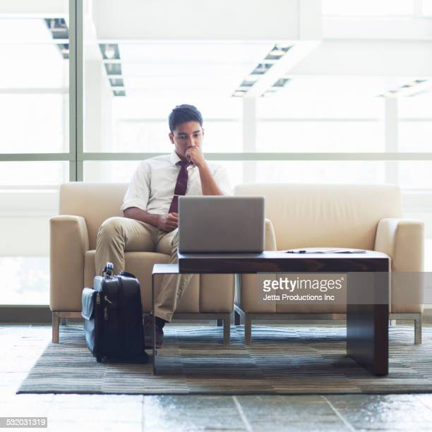 Indian businessman using laptop in office lobby