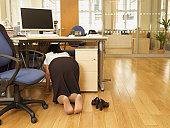 Indian businesswoman crawling under desk