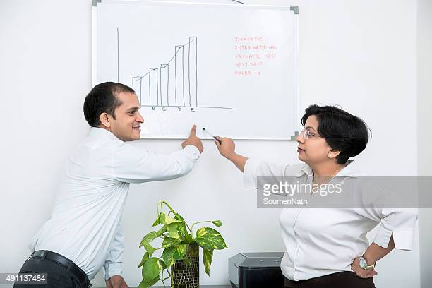 Indian Businesswoman discussing and explaining things to a colleague.