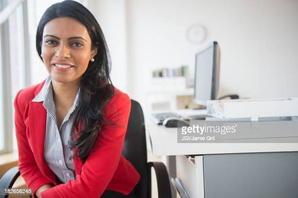 Indian businesswoman smiling at desk