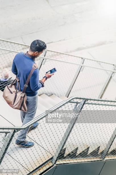 Indian businesswoman using cell phone on steps