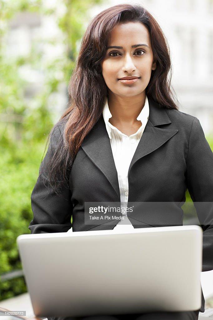 Indian businesswoman using laptop outdoors : Stock Photo