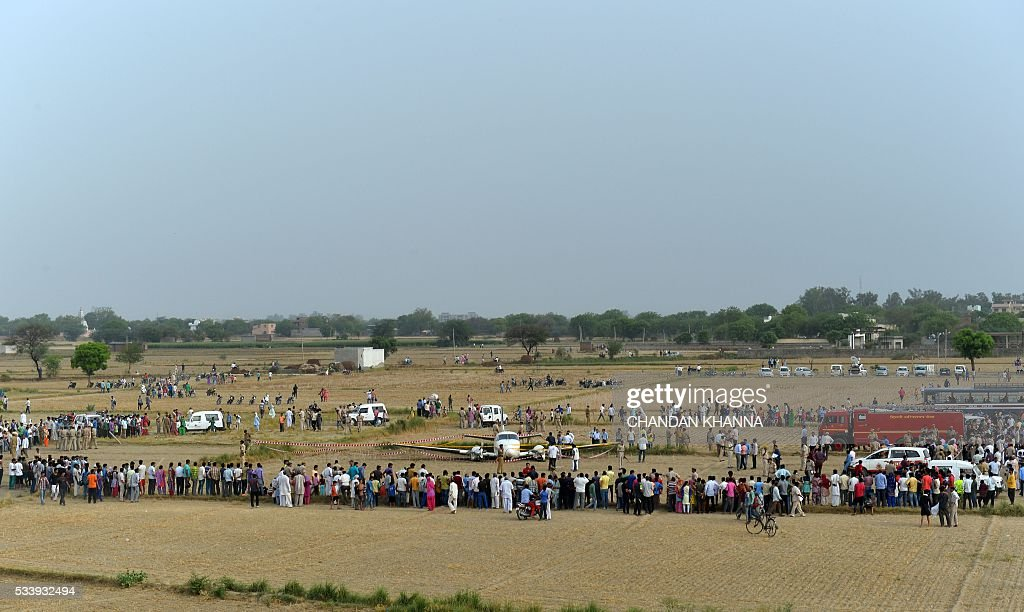Indian bystanders and emergency personnel gather around the wreckage of an aircraft which crash landed in a field on the outskirts of New Delhi on May 24, 2016. An air ambulance crash landed in a field near New Delhi airport on Tuesday, but all seven people on board survived, police said. / AFP / CHANDAN