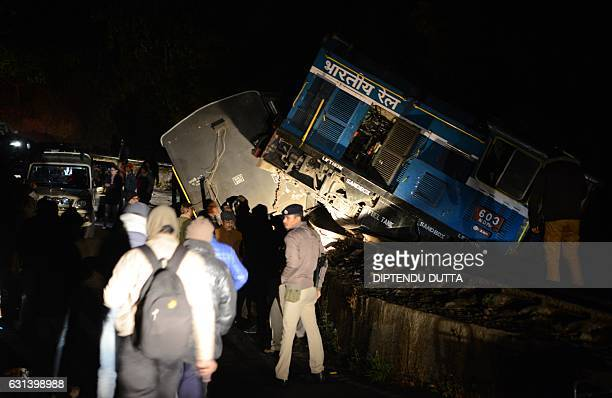 Indian bystanders and railway officials stand near the derailed engine and coaches of the Darjeeling Himalayan Railway known locally as the Toy Train...