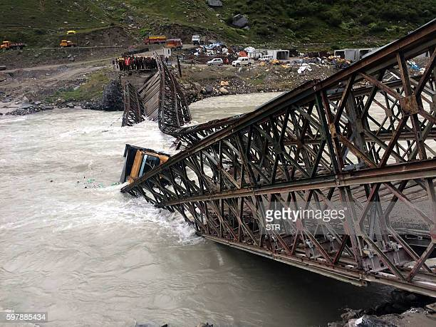 Indian bystanders and workers look on as a lorry lies in the waters of the River Chenab after a Bailey Bridge collapsed at Sissu some 200kms north of...