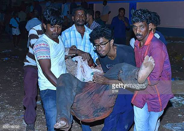 TOPSHOT Indian bystanders carry an injured man after an explosion and fire at The Puttingal Devi Temple in Paravur early April 10 2016 A major...