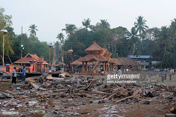 Indian bystanders gather among debris and building wreckage of The Puttingal Devi Temple in Paravur some 60kms northwest of Thiruvananthapuram on...