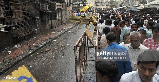 Indian bystanders gather near a bomb blast site at Opera House in Mumbai on July 18 2011 Scores of diamonds have been found on the devastated streets...