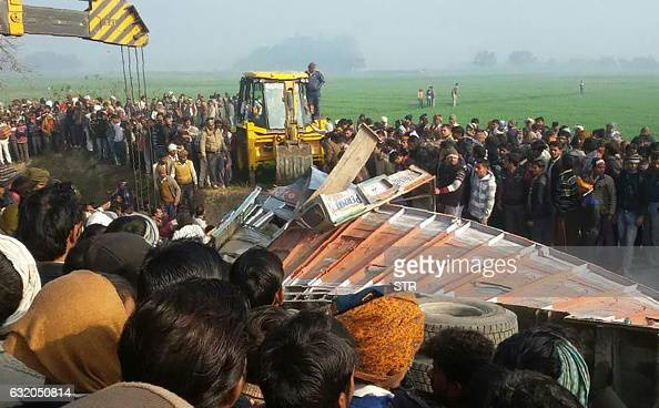 Indian bystanders gather near the scene of a bus crash in Etah in the state of Uttar Pradesh on January 19 2017 At least 15 children were killed and...