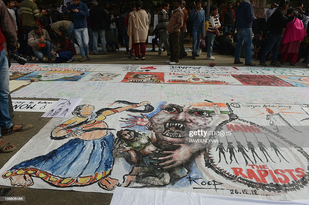 Indian bystanders look at a banner featuring images of 'government and rapists' as it lies on a road in New Delhi on December 30, 2012, after the cremation ceremony for a gangrape victim. The victim of a gang-rape and murder which triggered an outpouring of grief and anger across India was cremated at a private ceremony, hours after her body was flown home from Singapore. A student of 23-year-old, the focus of nationwide protests since she was brutally attacked on a bus in New Delhi two weeks ago, was cremated away from the public glare at the request of her traumatised parents.