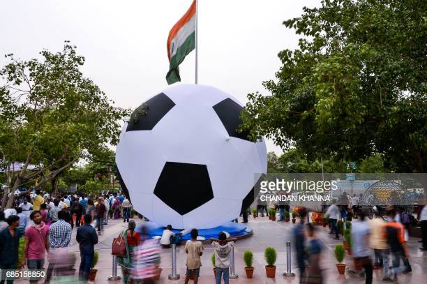 Indian bystanders look on as a balloon in the shape of a football is installed during the kick off function for the FIFA U17 World Cup in New Delhi...
