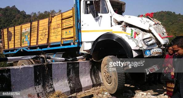 Indian bystanders walk past a damaged truck after it rammed into a concrete road barricade at an accident site near the village of Nonspung some...