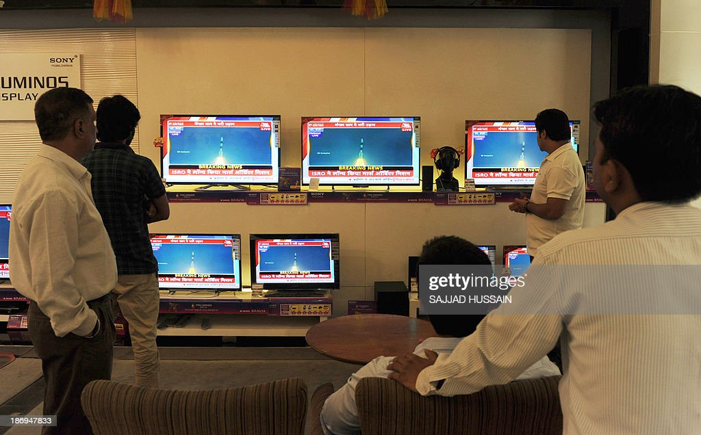 Indian bystanders watch a bank of screens showing the live telecast of the launch of India's Mars Orbiter Mission inside a showroom in New Delhi on November 5, 2013. India's first mission to Mars blasted off as the country aims to become the only Asian nation to reach the Red Planet with a programme showcasing its low-cost space technology.