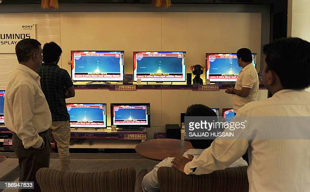 Indian bystanders watch a bank of screens showing the live telecast of the launch of India's Mars Orbiter Mission inside a showroom in New Delhi on...