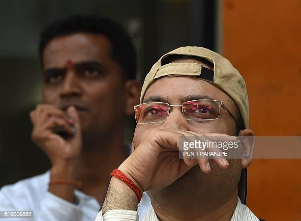 Indian bystanders watch a digital screen relaying the budget speech by Indian Finance Minister Arun Jaitley on the facade of the Bombay Stock...