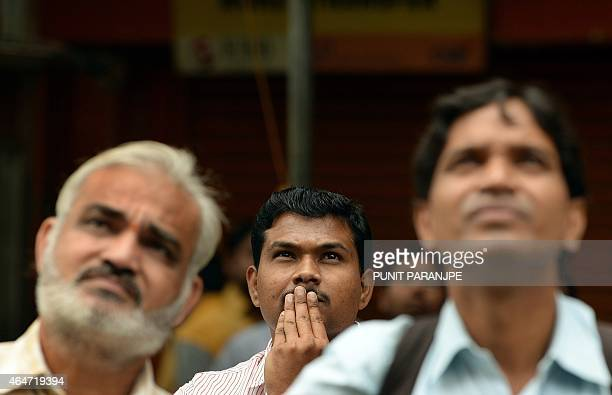 Indian bystanders watch a digital screen showing Indian Finance Minister Arun Jaitley delivering his Budget speech at Parliament in New Delhi at the...