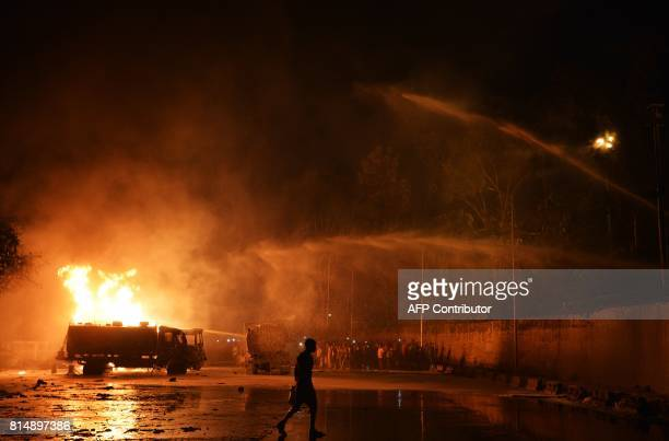 Indian bystanders watch as an oil tanker burns after catching fire near the entrance of Indian oil corporation depot in New Jalpaiguri area on the...