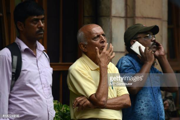 Indian bystanders watch the digital broadcast on the facade of the Bombay Stock Exchange displaying the benchmark share index SENSEX crossing 32000...