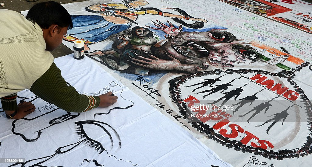 Indian bystanders write on a banner featuring images of 'government and rapists' as it lies on a road in New Delhi on December 30, 2012, after the cremation ceremony for a gangrape victim. The victim of a gang-rape and murder which triggered an outpouring of grief and anger across India was cremated at a private ceremony, hours after her body was flown home from Singapore. A student of 23-year-old, the focus of nationwide protests since she was brutally attacked on a bus in New Delhi two weeks ago, was cremated away from the public glare at the request of her traumatised parents.