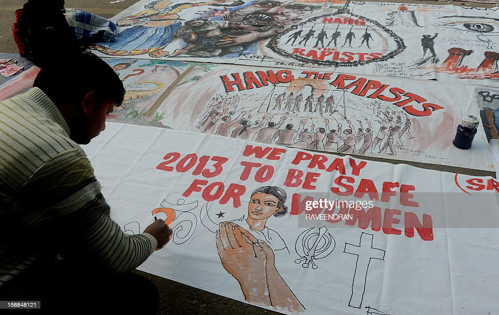 Indian bystanders write on a banner featuring images of 'government and rapists' as it lies on a road in New Delhi on January 1, 2013. The family of an Indian gang-rape victim said that they would not rest until her killers are hanged as police finalised their investigation before charges are laid against suspects this week. As the ruling Congress party reportedly pushed for tougher punishments for sex crimes, including chemical castration, authorities in New Delhi launched a hotline to improve safety for women in a city dubbed 'India's rape capital'.
