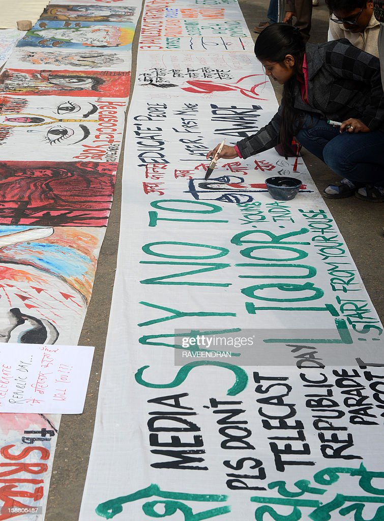 Indian bystanders write slogans on a banner featuring images as it lies on a road in New Delhi on December 30, 2012, after the cremation ceremony for a gangrape victim. The victim of a gang-rape and murder which triggered an outpouring of grief and anger across India was cremated at a private ceremony, hours after her body was flown home from Singapore. A student of 23-year-old, the focus of nationwide protests since she was brutally attacked on a bus in New Delhi two weeks ago, was cremated away from the public glare at the request of her traumatised parents.