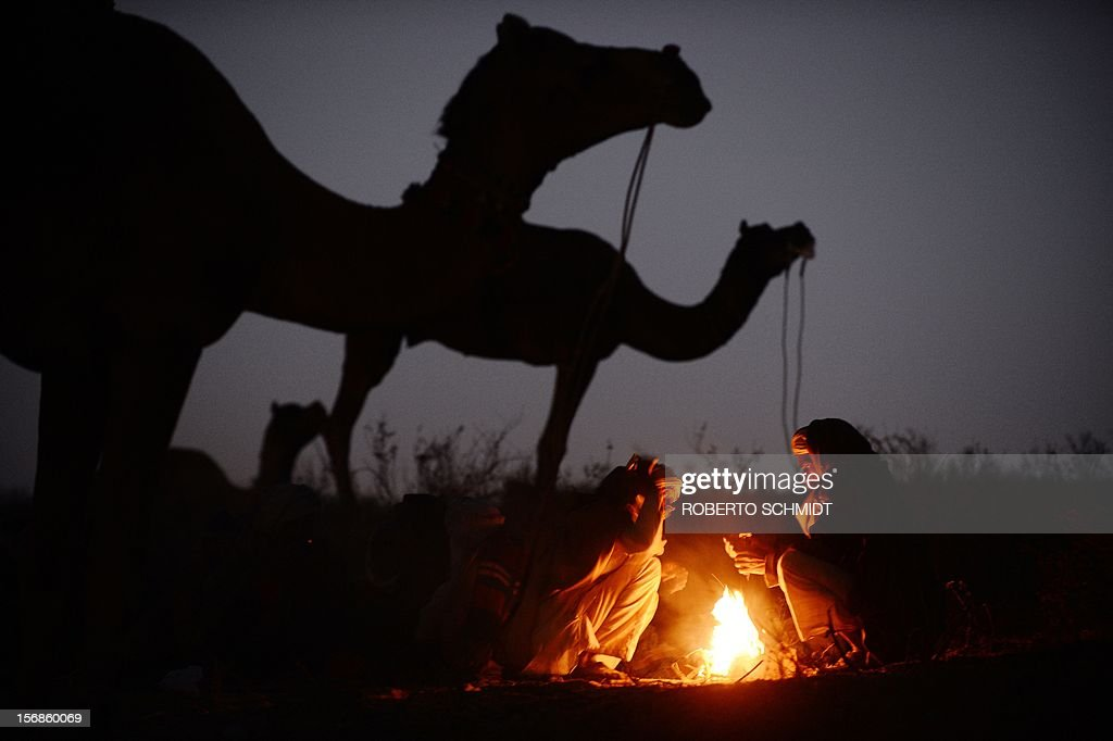 Indian camel owners sit around a fire near their camels for sale at the camel fair grounds in the outskirts of the small town of Pushkar on November 23, 2012. Thousands of livestock traders from the region come to the traditional camel fair where livestock, mainly camels, are traded. This annual five-day camel and livestock fair is one of the world's largest camel fairs. AFP PHOTO/ Roberto Schmidt