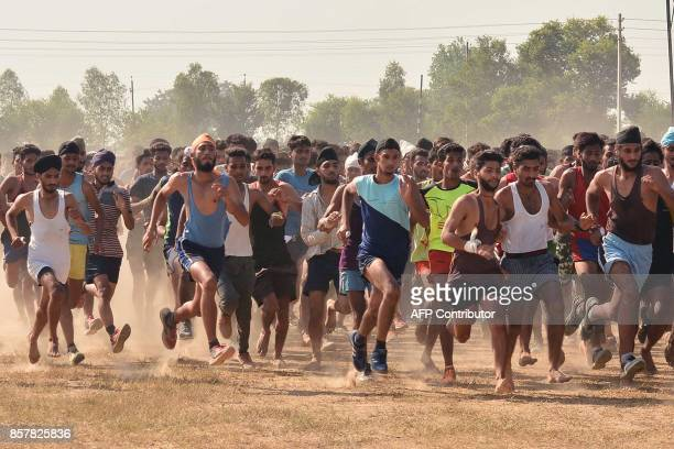 Indian candidates run during a physical fitness test at an Indian Army recruitment rally at Khasa some 15Kms from Amritsar on October 5 2017 / AFP...