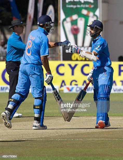 Indian captain Ajinkya Rahane celebrates 50 runs with batting partner Murali Vijay during the second game in a series of three One Day International...
