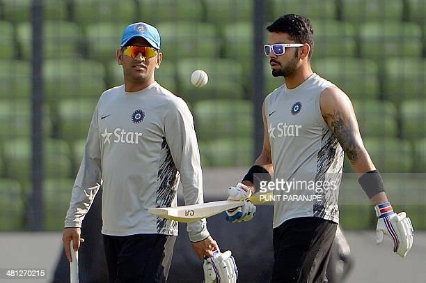 Indian captain Mahendra Singh Dhoni and teammate Virat Kohli arrive for a training session at The ShereBangla National Cricket Stadium in Dhaka on...