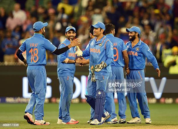 Indian captain Mahendra Singh Dhoni congratulates teammates after defeating Bangladesh in their 2015 Cricket World Cup quarterfinal match in...