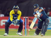 Indian captain Mahendra Singh Dhoni plays a stroke as Sri Lankan captain and wicketkeeper Kumar Sangakkara look on during the TriNation Championship...